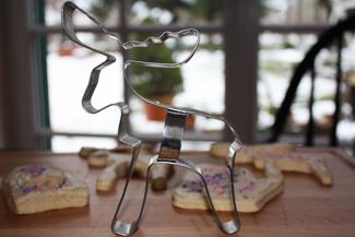 Keksausstecher mit Plätzchen im Hintergrund
